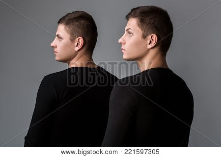 The two twin brother in the same black sweatshirts stand with their backs on the gray background. Both guys are looking aside