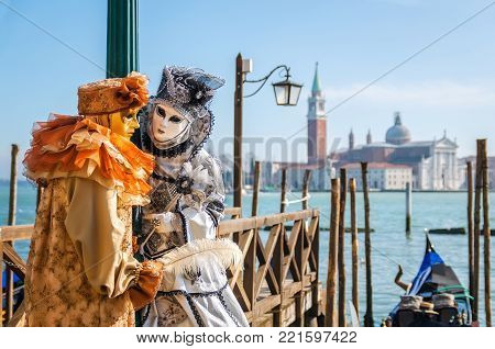 VENICE, ITALY -  FEBRUARY 27, 2014: Carnival of Venice. Two people in beautiful carnival costumes in background blue lagoon of Venice and gondola.