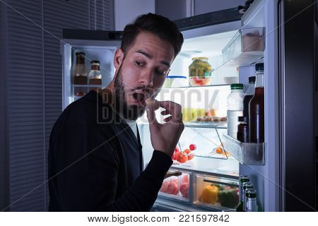 Close-up Of A Young Man Eating Cookie Near Open Refrigerator
