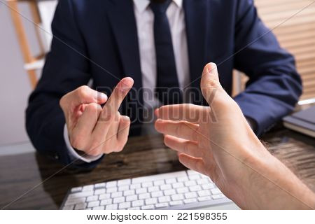 Businessman Showing Fuck Off With The Middle Finger To The Person Shaking Hand In Office