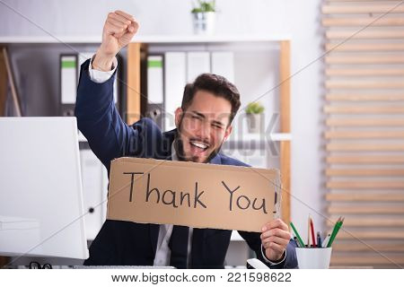 Smiling Young Businessman Raising His Arms While Holding Cardboard With Thank You Text