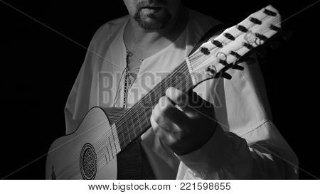 Man playing spanish renaissance instrument vihuela de mano over black
