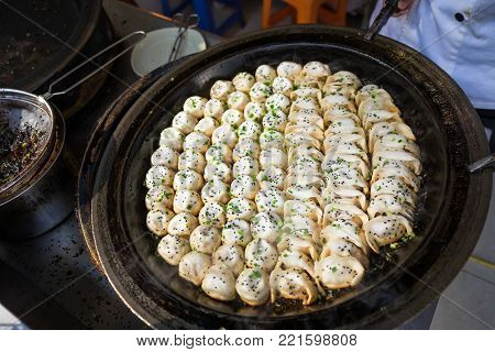 Sheng Jian Bao and Guo Tie being cooked - Shanghai pan fried dumplings in traditional pan - Full pan
