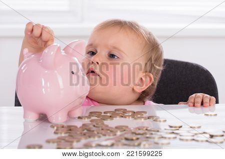 Cute Little Baby Girl Inserting Golden Coin In Piggybank