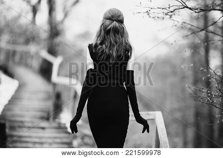 Black and white art monochrome photography. Striking girl with long hair in black clothes. Black and white creative photography. Black and white conceptual image. Beautiful black and white background.