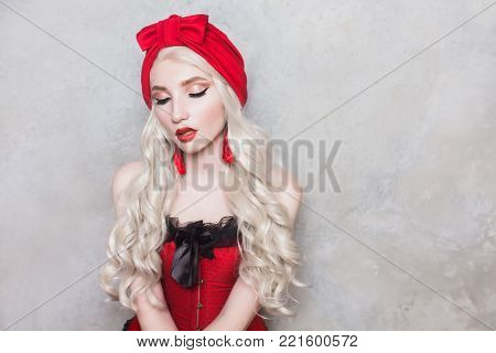 Luxurious blonde woman with beautiful long white hair. Beautiful woman in a red turban. Sexy young blonde woman with red lips on a gray background. Attractive woman with red earrings. Luxury blonde woman
