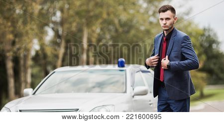 Successful politician in a dark business suit with a red tie on the background of a gray car. Stylish politician. Politician on the background of the machine. The politician looks into the distance