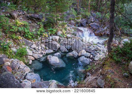 Blue pool with natural hot stream water near mountain river in Hoytogol, Buryatia, Eastern Sayan.
