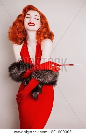 Red-haired retro woman with curly hair in red retro dress and long retro gloves smoke. Retro girl is dressed in retro style with fur and the mouthpiece with a cigarette. A retro woman with pale skin and lred hair