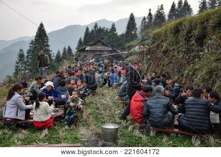 GUIZHOU PROVINCE, CHINA - CIRCA DECEMBER 2017:  A group of people different ethnic minority sit together on the occasion of wedding feast.