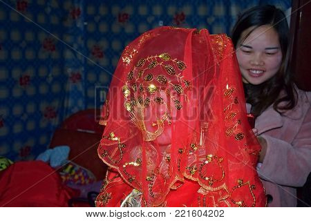 GUIZHOU PROVINCE, CHINA - CIRCA DECEMBER 2017: A wedding, chinese ethnic minority Yao and Shui. A bride covered with red wedding veil.