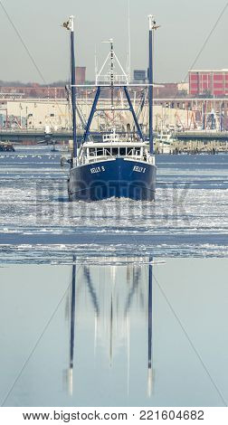 New Bedford, Massachusetts, USA - January 10, 2018: Fishing vessel Kelly S crossing icy New Bedford harbor