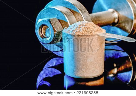 Measuring scoop with whey protein mixture on a background of a metal dumbbell.