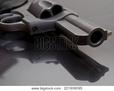 The barrel of a stainless steel  revolver laying upon a glass surface