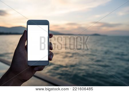 Mockup image of a hand holding and showing white mobile phone with blank desktop screen in front of the sea and sky background