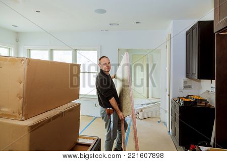 Carpenter installing cabinets and counter top in a kitchen. insrall counter top kitchen