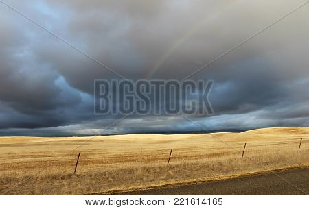 Dark gray storm clouds contrast with dry yellow grass fence and rainbow on country road Santa Ynez California