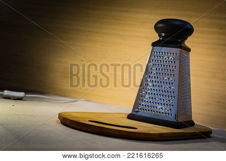 A metal grater for cheese with a plastic handle stands on a wooden board in a ray of light warm, appetizing color.
