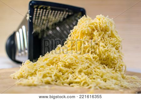 A large pile of yellow cheese grated rests on a wooden stand in the background of a metal grater. Still life in warm tones, the view from the side on level of eye look.