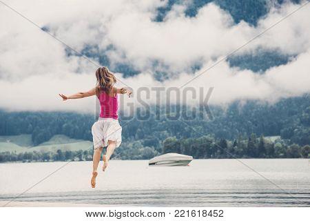 Woman jumping at the lake Garda. Italy