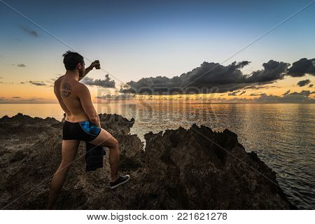 SAN ANDRES ISLAND, Colombia _ Circa March 2017. Man Cheering the Caribbean Sunset Over the Ocean on the Volcanic Rock Shore during the Evening