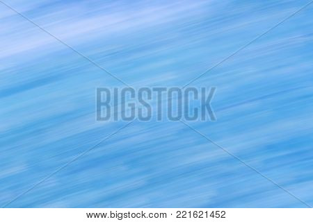 Abstract blurred sky and cloud with movement effect.  Natural blue background with directional blur, motion effect and long exposure. Diagonal lines and strips.