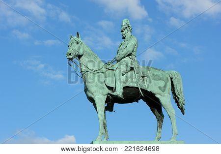 The monument of Emperor Wilhelm I. Figure of the Emperor Wilhelm I on a horse on a background of blue sky. Monument is located near the City hall Hamburg-Altona.