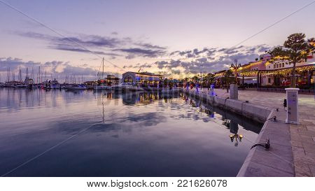 Beautiful Marina in Limassol city Cyprus at dusk. A modern, high end life and newly developed port with docked yachts, restaurants, shops, a landmark for waterfront promenade. View of the commercial area at sunset.