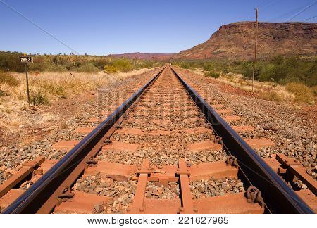 Railway line running beside Mount Nameless near the town of Tom Price in Western Australia. Tom Price exists solely to support the mining of iron ore from this area of the Pilbara.