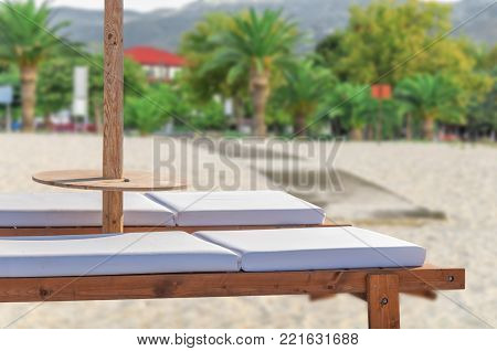 Two Empty Sun Bed At Public Sandy Beach For Relaxation With Green Natural Background