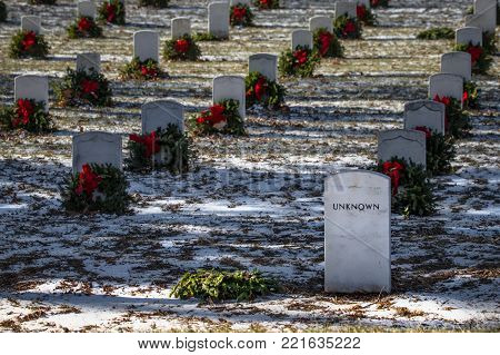A fallen wreath on the grave of an Unknown US service member at a national cemetery.