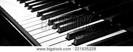 The keys of a old piano set in a black and white film noir look.