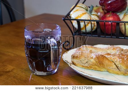 A danish, coffee and fruit at breakfast time