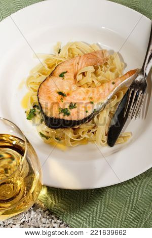 grilled salmon steak with tagliatelle on a plate and a glass of white wine