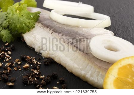 fresh herring fillet with slice lemon, parsley and crushed pepper on slate