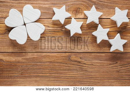 White wooden flower and stars on brown wooden background, copy space, top view. Abstract white flower on wooden background. One flower head on brown wood table background.