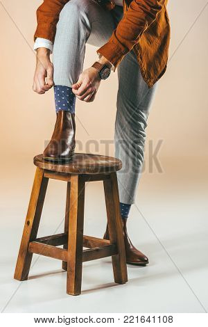 partial view of man tying shoelaces while standing on wooden chair with one leg