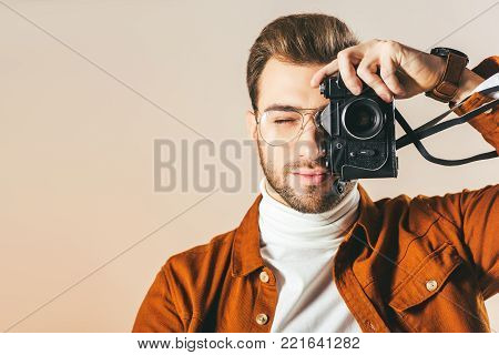 obscured view of handsome man taking picture on photo camera isolated on beige
