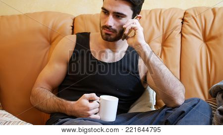 Young man talking on phone while drinking coffee at home, sitting on couch