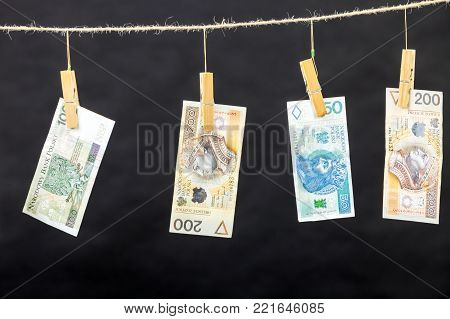 Banknotes cash money hang on laundry line on black background.