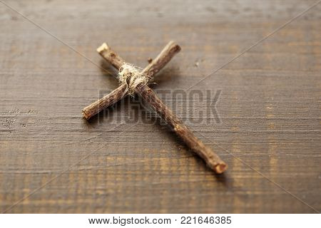 Wooden homemade Christian cross tied with a canvas thread close up. A symbol of faith on a wooden surface.