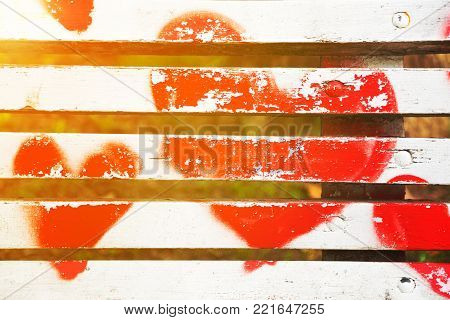 Red hearts painted on a white wooden bench in Love concept with golden glow from the sun.
