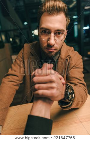 camera point of view focused man arm wrestling with opponent in cafe