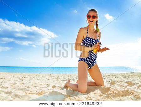 Sun kissed beauty. happy active woman in beachwear on the beach applying suntan lotion