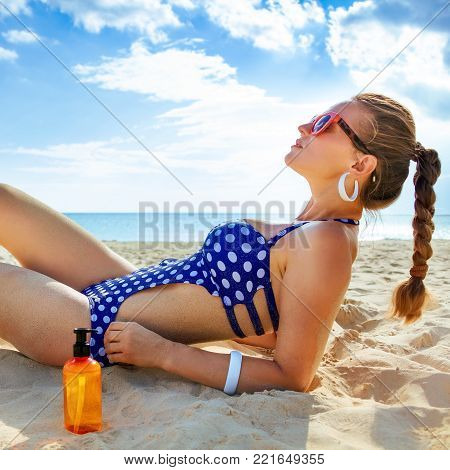Sun kissed beauty. active woman in beachwear on the seacoast with sun block laying