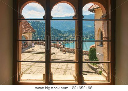 Bled, Slovenia - July 05, 2017: View of the upper yard of Bled Castle, the oldest Slovenian castle and one of the most visited tourist attractions in Slovenia, through the fortress window.