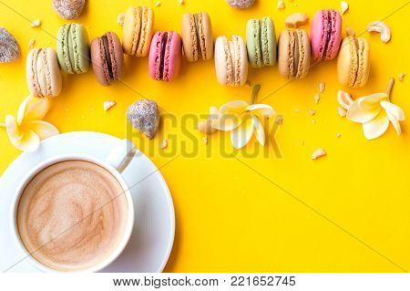 French macaroon cake and cup of coffee. Macaroons with white flowers on a yellow background flat lay.