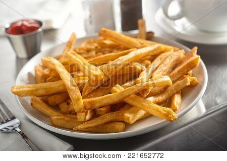 A plate of delicious crispy french fries served in a diner on a stainless steel countertop.