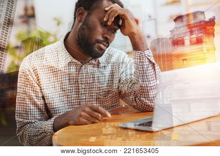 Bad mood. Low-spirited office worker touching forehead and holding telephone in right hand while sitting at his workplace