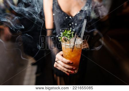 girl in a black dress is holding an alcoholic orange cocktail with ice and a twig of dry and fresh mint on the background of smoke.